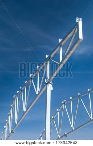 Galvanized steel roof truss construction frames with deep blue sky in the background