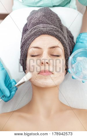beautician applies face mask with a brush to the beautiful young woman in Spa salon. cosmetic procedure skin care. Microdermabrasion poster