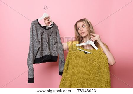 Woman choosing her fashion outfit. Girl thinking what to wear after the shopping.