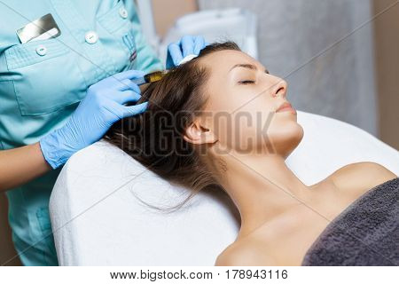 Needle mesotherapy. Cosmetic been injected in woman's head. Thrust to strengthen the hair and their growth
