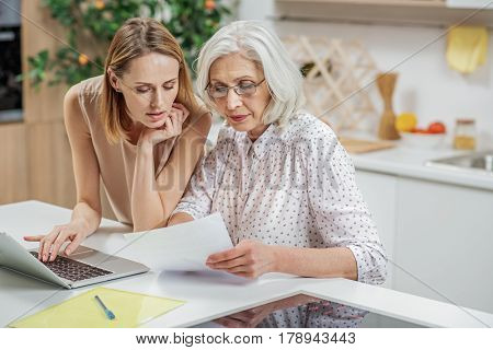 Senior woman is reading document with concentration. Her daughter is standing and helping her. She is typing on laptop