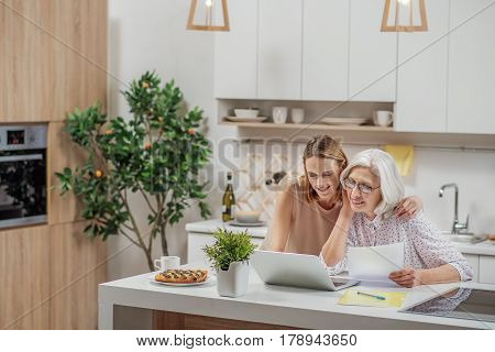 Portrait of cheerful young woman explaining her mother how to pay utility bills through internet. She is embracing her and smiling. Senior lady is holding documents in kitchen