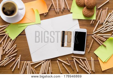 Buy stationery online. Flat lay top view shot of workplace of designer or artist with credit card, lots of pencils, mobile phone, sketchbook, sticky memo notes and cup of morning coffee on wooden desk
