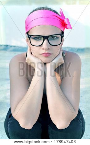 Funky woman with blonde hair, brown eyes and dark eye make-up is wearing a neon pink headband with a bow and black framed glasses.