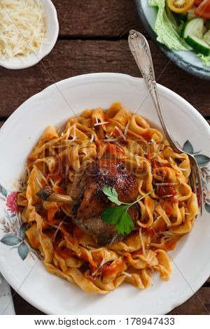 Italian homemade pasta, pappardelle with tomato sauce and braised rabbit, top view close-up.