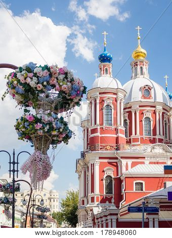 The baroque church of Saint Clement of Rome in Moscow with flowers on the foreground.