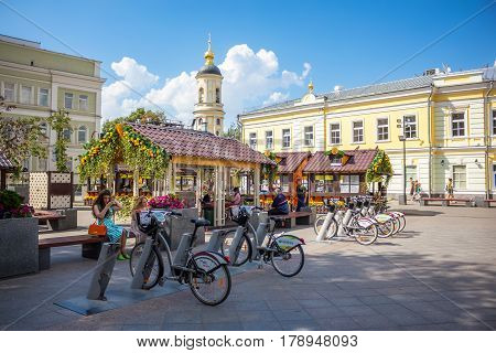MOSCOW - AUGUST 7 2016: People sitting near bicycle rental station on Pyatnitskaya street. The project of urban bike rental started in 2013.