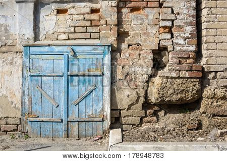 Large vintage barn doors with obsolete blue paint and weathered brick wall in background