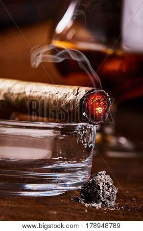 close view on burning smoking cuban cigar with ash