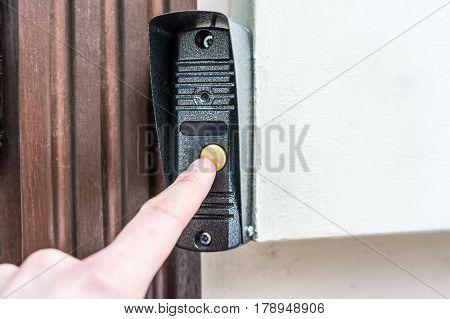 Hand pressing modern door bell button on wall