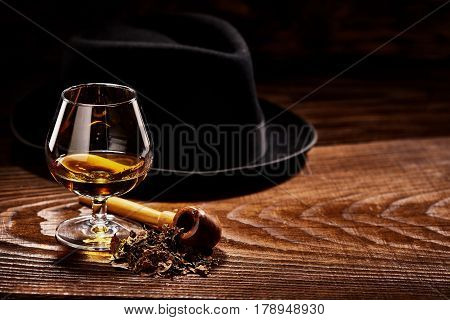 Glass of cognac and pipe with tobacco with black hat defocused on second background on wooden table