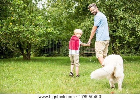 Father and child walking with dog in the garden