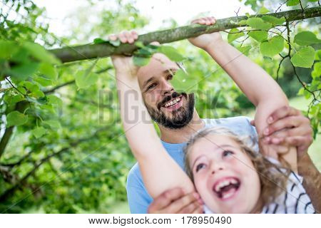 Father and daugther playing and climbing tree with support