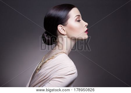 Portrait of young brunette woman against a dark background. Mysterious bright image of a woman with professional makeup. The sensuality and mystery of women. Hair care and skin