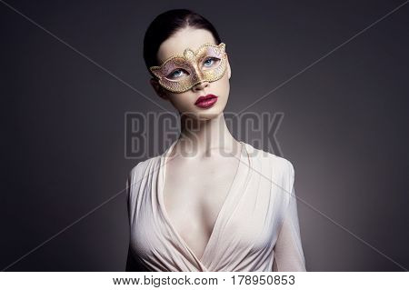 Portrait of young brunette woman against a dark background. Mysterious bright image of a woman with professional makeup. Sensuality and mystery of women. Hair care and skin. Face facial mask girls