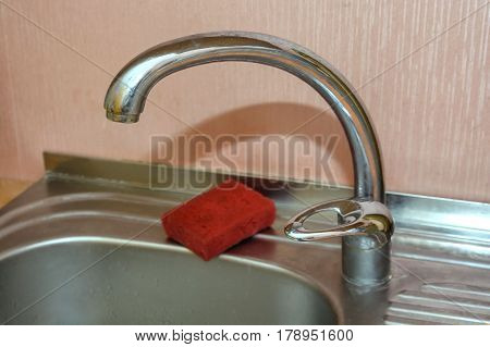 Modern kitchen sink with chrome water tap and sponge