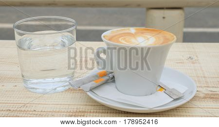 Cup of capuccino and a glass of water on a wooden table
