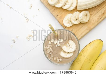 Useful smoothies with a banana and oatmeal on a white background. View from above
