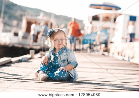 Funny baby girl 1-2 year old sitting on wooden pier wearing denim clothes outdoors. Looking away. Childhood. Summer time.
