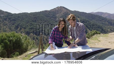 Two people looking at map searching route