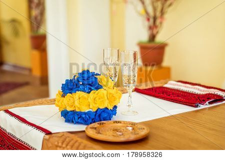 bouquet, rings and glasses of champagne on the embroidered towel on the table in the registry office during the ceremony in Lviv, Ukraine