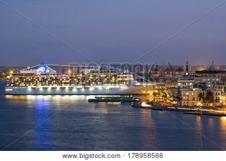 HAVANA,CUBA - MARCH 9, 2017 : A modern cruise ship is docked at the port of Havana with the old city illuminated at night