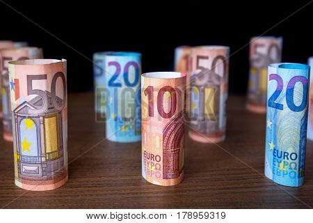 Rolled up euro banknotes on the desk. Selective focus