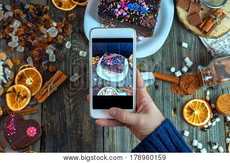 White smartphone in a woman's hand takes a piece of cake and sweets view from the top