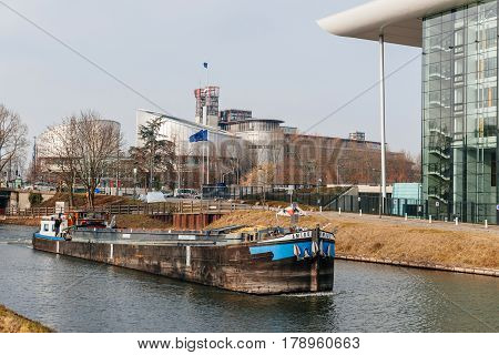 STRASBOURG FRANCE - FEB 12 2017: Amigo canal barge boat transporting coal on Ill river with the European Court of Human Rights in the background