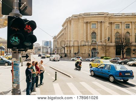 BUCHAREST ROMANIA - APR 1 2016: Pedestrians waiting to cross the Calea Victoriei Boulevard avenue with the The National Museum of Art of Romania in the background