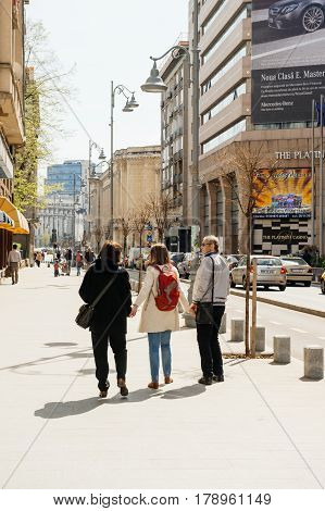 BUCHAREST ROMANIA - APR 1 2016: Happy adult daughter spending time with her parents - walking on the streets of Bcuharest - holding both parents by hand