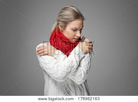 Young woman in warm clothes shivering from cold on gray background