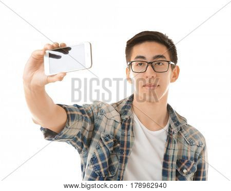 Young Asian man taking selfie on white background