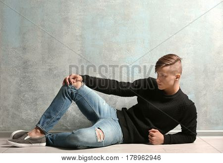 Handsome young man near textured wall