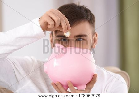 Happy young man putting coin into piggy bank, closeup