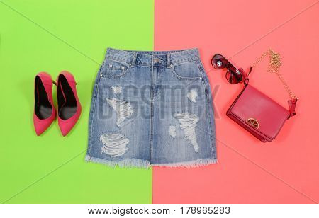 Blue denim skirt,bag, sunglasses, shoe isolated on green and pink background