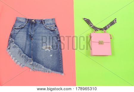Blue denim skirt and handbag isolated on green and pink background