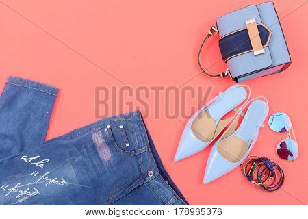 Stylish woman Handbag and cosmetics,makeup accessories,jeans on orange background