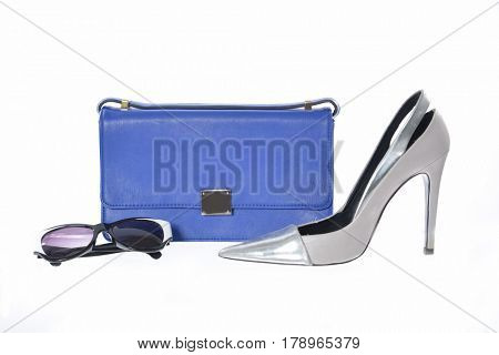 Fashion concept. Blue handbag ,black shoes and glasses on a white background