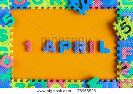 April Fool's Day, calendar date April 1. Toy puzzle frame and letters.