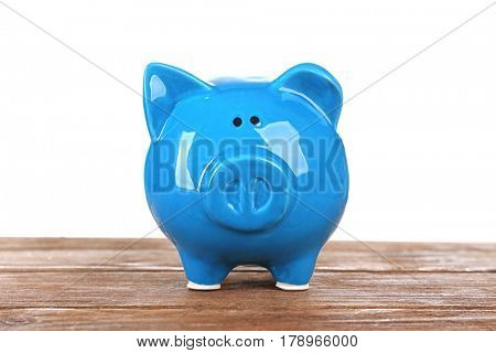 Blue piggy bank on wooden table against white background