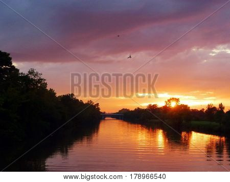 Gorgeous colors sunset night time sky over river and trees