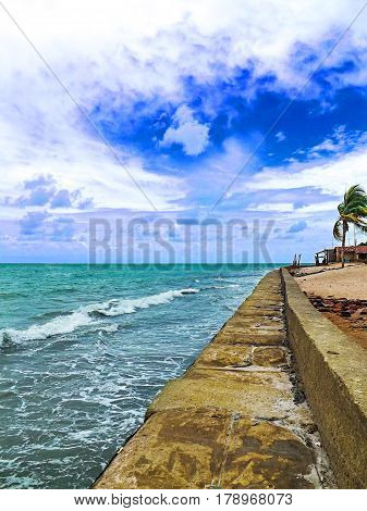Tropical beach with rocks and rocks. Sand with cloudy sky. Nature of tropical island. Exotic seaside digital illustration. Beautiful sea water and sunny beach. Relaxing travel image. Alagoas, Brazil.