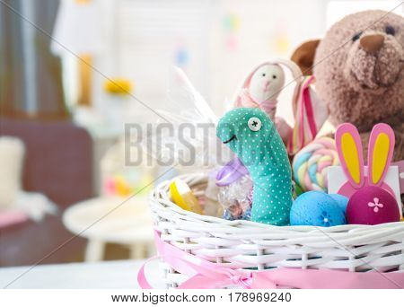 Beautiful Easter basket with traditional colorful symbols and sweets, closeup