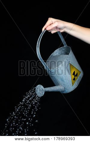 Environmental pollution concept. Woman pouring toxic water from can against black background
