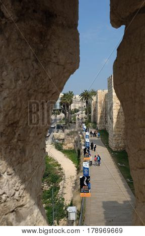 JERUSALEM ISRAEL - MARCH 25 2017: View through the loophole of the Jaffa Gate on the path along fortress wall. Inscriptions: announcement of the concert and advertising of the health insurance fund