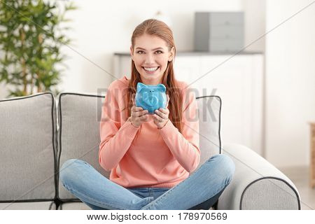 Beautiful young woman with piggy bank at home
