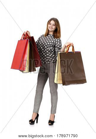Young beautiful brunette woman with some shopping bags, isolated on white background