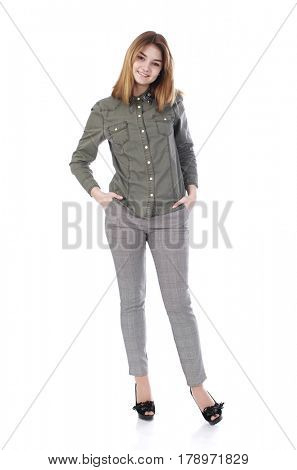 Young beautiful blonde girl in gray trousers and green shirt, isolated on white background