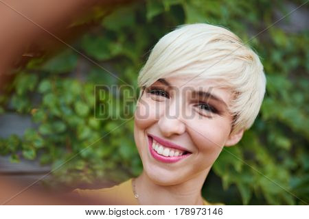 Portrait of an urban boyish blonde millennial girl giving a toothy smile and taking a photo herself with a mobile smart phone in front of a leafy background.